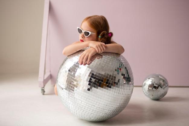 Full shot girl posing avec boule disco