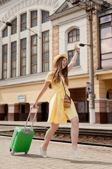 Full shot happy woman transportant des bagages