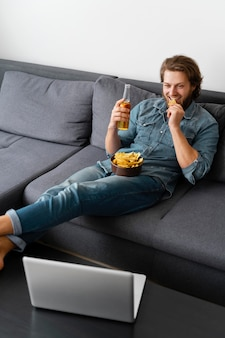Full shot homme assis sur le canapé avec boisson