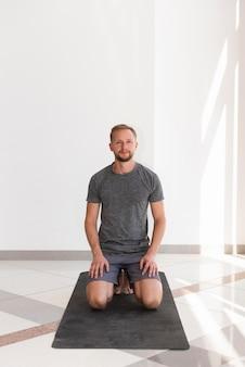 Full shot homme assis sur un tapis de yoga