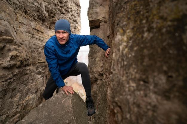 Full shot homme escalade à travers les rochers