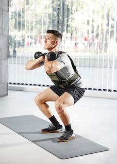 Full shot homme faisant des squats avec haltère