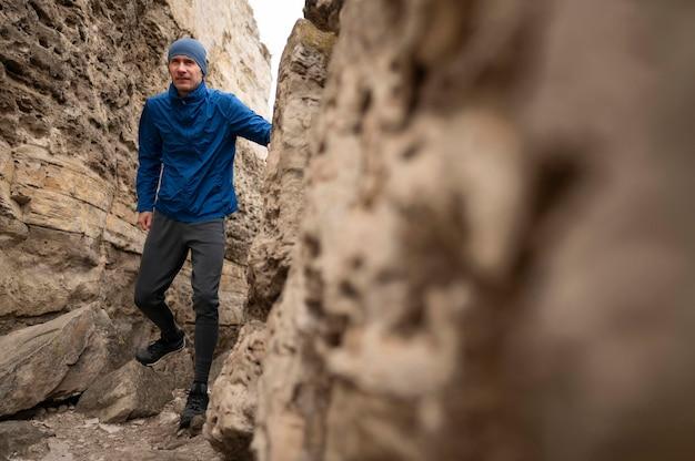 Full shot homme marchant à travers les rochers