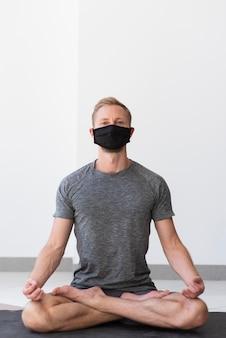 Full shot homme avec masque facial faisant sukhasana pose à l'intérieur sur tapis