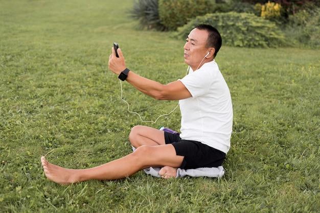 Full shot homme regardant téléphone