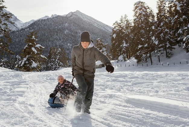 Full shot membres de la famille jouant dans la neige