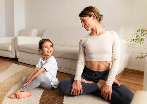 Full shot mère et fille assise sur le sol