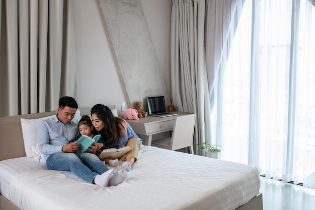 Full shot parents et enfant au lit