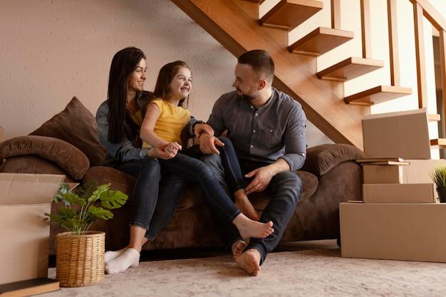 Full shot parents et enfant sur le canapé