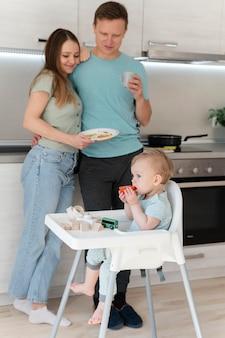 Full shot parents et enfant dans la cuisine