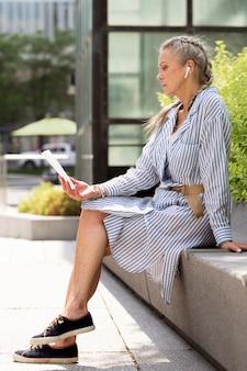 Full shot senior woman lisant à l'extérieur