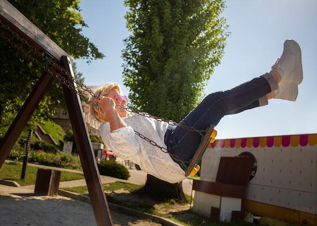 Full shot senior woman on swing