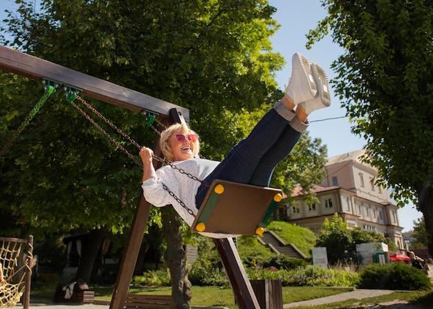 Full shot smiley senior woman on swing
