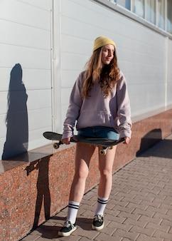 Full shot teen girl holding skateboard