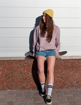 Full shot teen girl sitting on skateboard