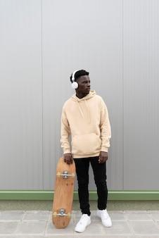 Full shot teen holding skateboard