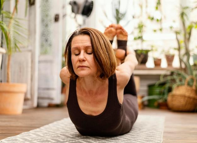 Full shot vieille femme sur tapis de yoga