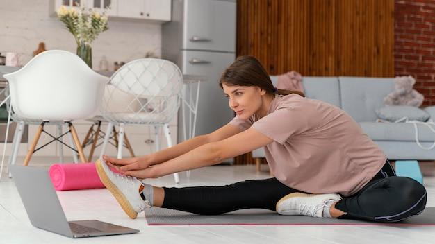 Full shot woman stretching avec ordinateur portable