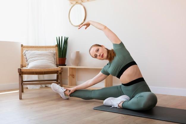Full shot woman stretching sur tapis à l'intérieur