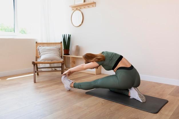 Full shot woman stretching sur tapis à la maison