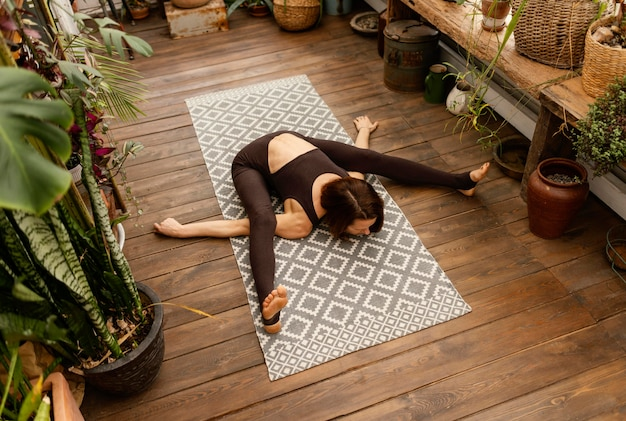 Full shot woman stretching sur tapis de yoga