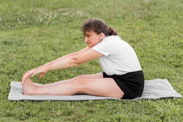 Full shot woman stretching sur tapis
