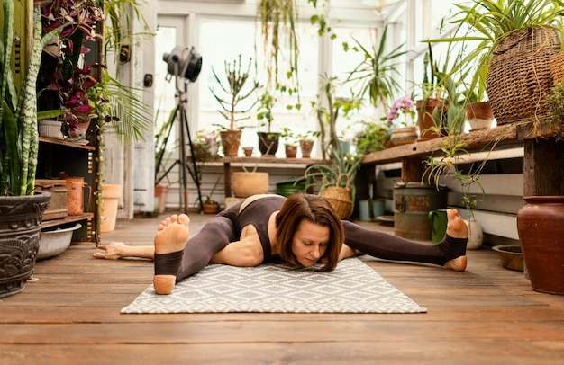 Full shot woman stretching sur tapis