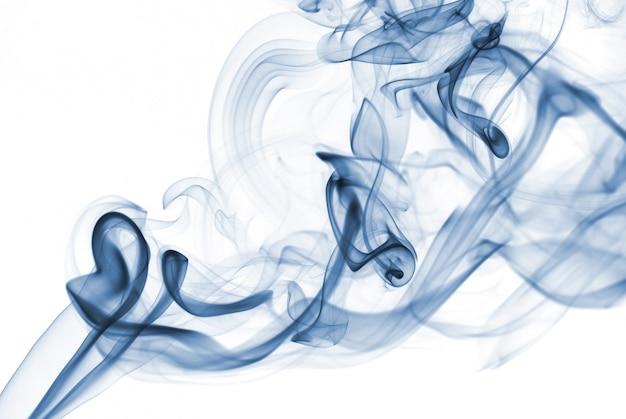 Fumée abstraite bleue des bâtons aromatiques sur fond blanc.