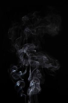 Fumée blanche abstraite tourbillonne sur fond noir