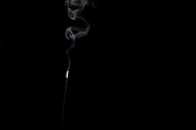 Fumée blanche d'un bâton d'encens sur fond noir