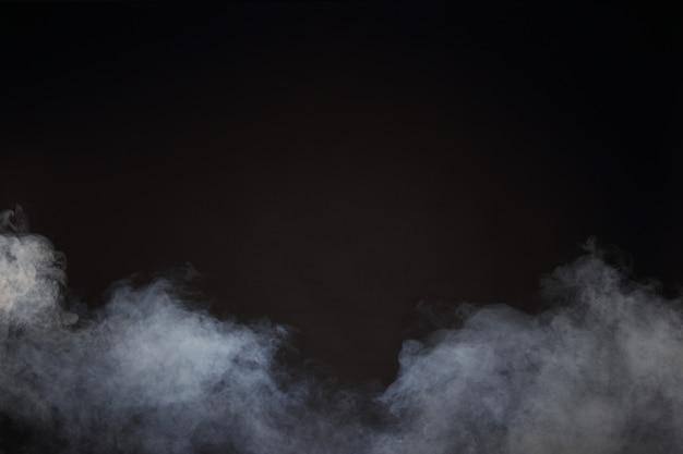 Fumée blanche et brouillard sur fond noir, nuages de fumée abstraits