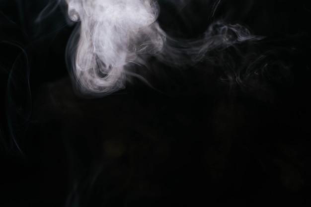 Fumée blanche ondulée sur fond noir