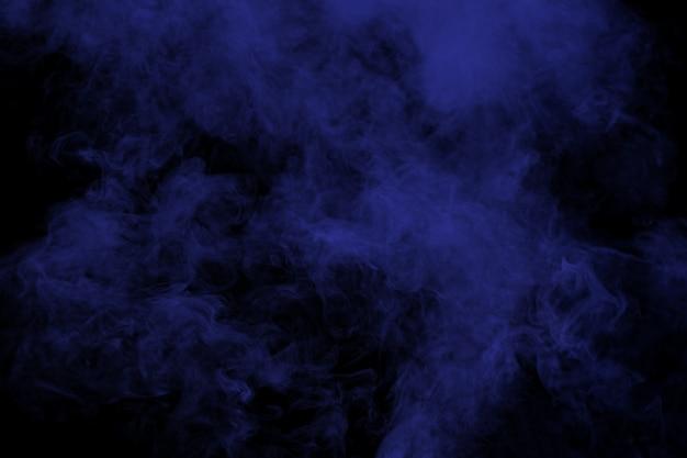 Fumée bleue abstraite sur fond noir.
