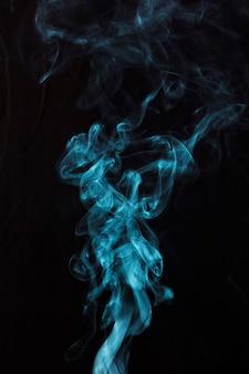 Fumée bleue sur fond noir avec espace de copie pour l'écriture du texte