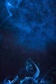 Fumée bleue et jet d'eau sur fond noir