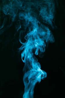 Fumée bleue répandue sur fond noir