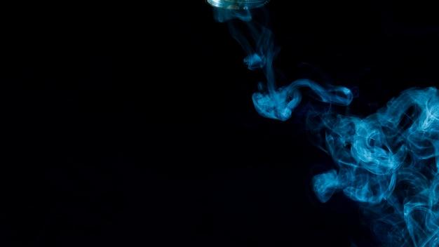La fumée bleue se propage sur fond noir
