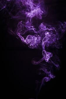 Fumée colorée flottant dans l'air sur fond sombre