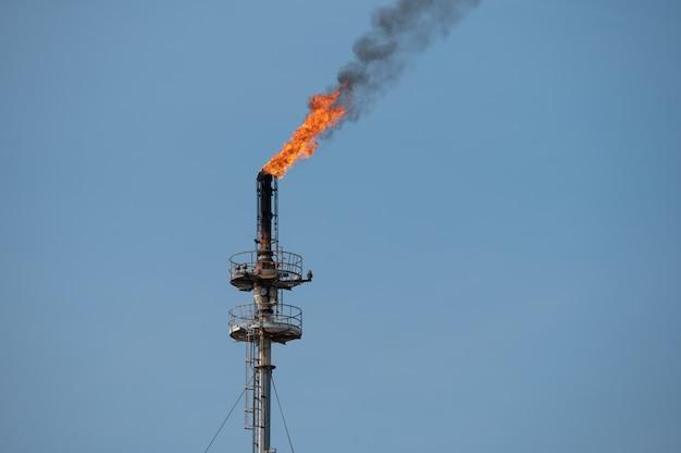 Fumée et flamme provenant d'une raffinerie de pétrole