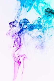 Fumée flottant colorée dans l'air sur fond blanc