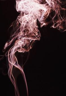 Fumée flottant dans l'air sur fond sombre