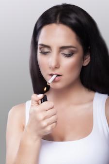 Fumée. une jeune fille allume une cigarette en la tenant dans la bouche. interdiction de fumer.