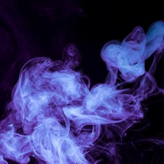 La fumée pourpre se propage sur le fond noir