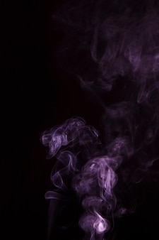 La fumée rose se répand sur le fond noir
