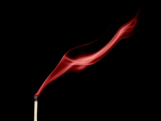 Fumée rouge d'un match éteint isolé