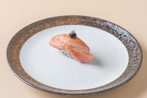 Fumée de saumon cru sur riz à sushi