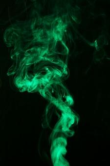 Fumée verte brillante sur fond noir