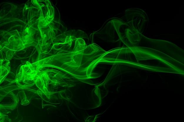 Fumée verte sur fond noir, concept d'obscurité