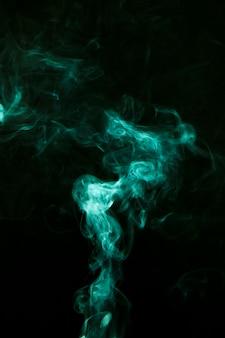 La fumée verte se déplace sur un fond noir et sombre