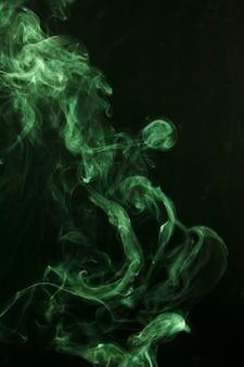 La fumée verte se propage sur le fond noir